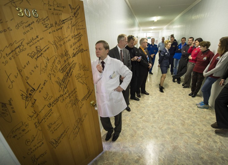 October 23, 2012: Chief Epidemiologist of the Gagarin Cosmonaut Training Center, Sergei Savin, and others watch and wait for Expedition 33/34 crew crew members, Flight Engineer Kevin Ford, Soyuz Commander Oleg Novitskiy, and Flight Engineer Evgeny Tarelkin to depart a room at the Cosmonaut Hotel on the morning of their Soyuz launch to the International Space Station in Baikonur, Kazakhstan. Doors at the Cosmonaut hotel are traditionally signed by each crew member before departing the hotel. (NASA/Bill Ingalls/AFP/Getty Images)