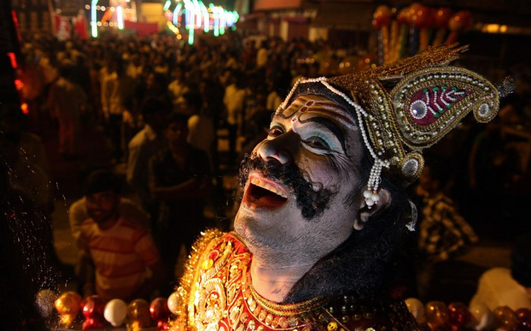 An Indian artist performs during a Dussehra festival procession in Allahabad on late October 22, 2012. The Hindu festival of Dussehra, during which a giant effigy of Ravana is burnt and which celebrates the victory of good over evil, culminates on October 24. (STR/AFP/Getty Images)
