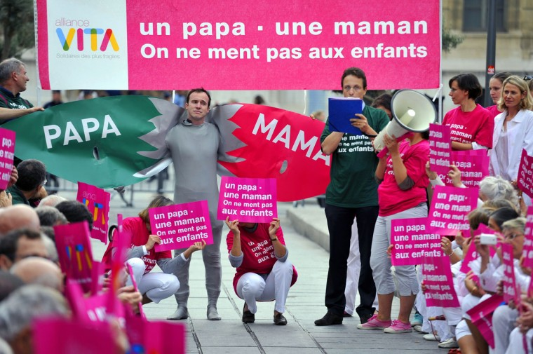 People stand under a banner reading 'A dad, a mum, we don't lie to children' take part in a demonstration called by the 'Alliance VITA' association against gay marriage and adoption by same-sex couples in Marseille, southeastern France. France on October 10 named October 31 as the date when a draft law authorising gay marriage will be approved by government ministers, amid mounting opposition to the proposed legislation. (Gerard Julien/AFP/Getty Images)