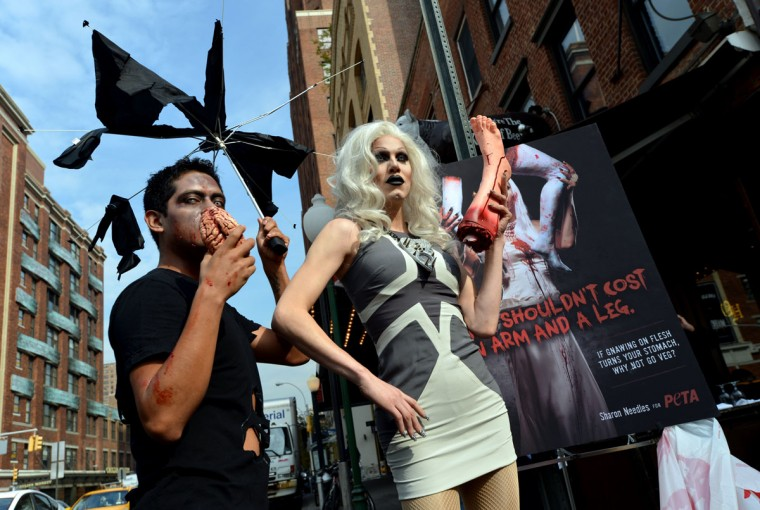 Goth star and drag performer Sharon Needles, right, holds a mannequin leg with a man dressed as a zombie after she unveiled PETA's first-ever Halloween campaign in New York. (Stan Honda/AFP/Getty Images)
