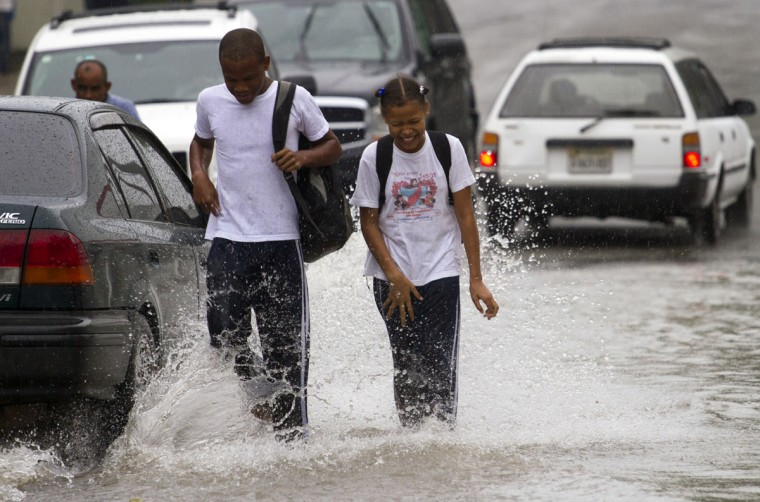 October 24, 2012: Dominican school children walk in the flooded streets of Santo Domingo before the arrival of Hurricane Sandy. (Erika Santelices/AFP/Getty Images)