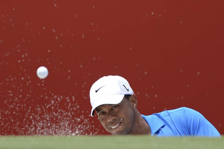 US golfer Tiger Woods hits out of the bunker on the ninth hole during the first round of the CIMB Classic golf tournament at the Mines Resort and Golf Club in Kuala Lumpur. (Mohd Rasfan/Getty Images)