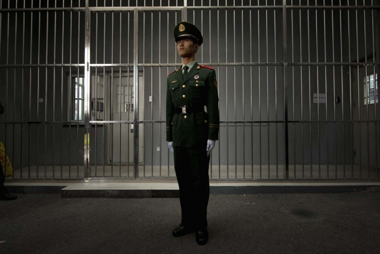A paramilitary guard stands before the bars of a main gate to the No.1 Detention Center during a government guided tour in Beijing. The rare visit to the facility, which has capacity for 1,000 inmates, was opened to the foreign media as Beijing prepares for the 18th Congress of the Communist Party of China. (Ed Jones/Getty Images )