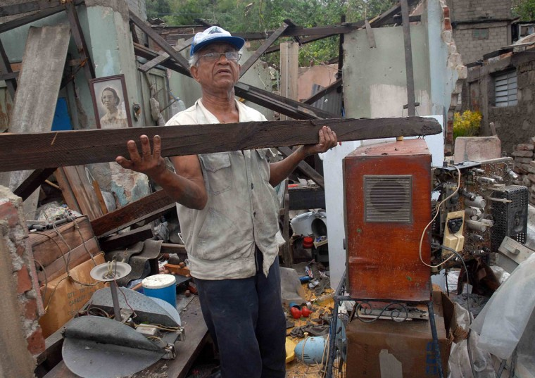 October 25, 2012: A Cuban clear of debris his house, demolished by Hurricane Sandy, in Santiago de Cuba, Cuba. (AFP PHOTO/AIN'Miguel Rubiera Justiz/AFP/Getty Images