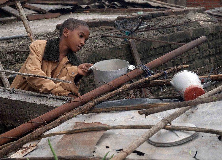 October 25, 2012: A Cuban child retrieves utensils from his home, demolished by Hurricane Sandy, in Santiago de Cuba. (AIN/Miguel Rubiera Justiz/AFP/Getty Images)
