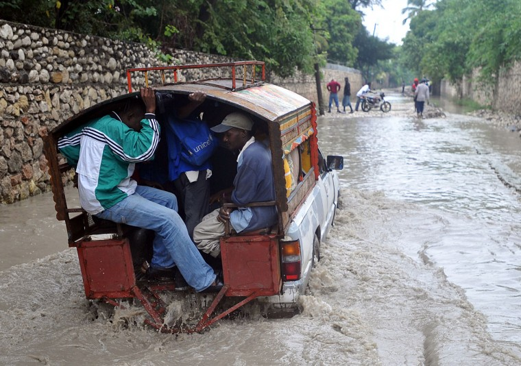 October 25, 2012: Haitians travel a flooded street in the aftermath of Hurricane Sandy in Port-au-Prince, Haiti. (Thony Belizaire/AFP/Getty Images)