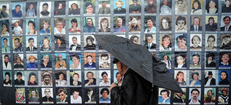 A man looks at the portraits of the Nord-Ost musical hostage drama victims at the Dubrovka Theatre in Moscow during a commemoration ceremony to mark the 10th anniversary of the tragedy. A total of 912 people, many of them children, were held hostage in the Dubrovka theatre for three days after coming to watch Nord Ost, a popular musical. A raid by Russian special forces to free the hostages led to the death of 130 people, including 17 actors and musicians, most of them from a powerful gas that police had pumped into the theater before the raid. (Yuri Kadobnov/AFP/Getty Images)