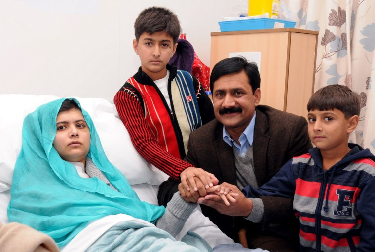 Pakistani schoolgirl Malala Yousafzai, who was shot in the head by Taliban gunmen for campaigning for the right to an education, sits on her bed and holds hands with her brothers Khushal Khan (3rd R) and Apal Khan (R) and father Ziauddin Yousufzai, at the hospital in Birmingham on October 25, 2012. The response of Pakistan to the shooting of the Malala by the Taliban was a 'turning point' for the country, her father said at the British hospital where she is recovering. (Queen Elizabeth Hospital/University Hospitals Birmingham/AFP/Getty Images)
