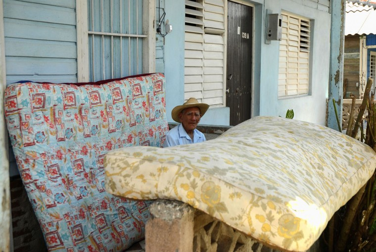 A man sits next to matress drying on a porch after the passage of Hurricane Sandy in Antillas, Holguin Province, Cuba, some 750 kilometers east of Havana. Hurricane Sandy claimed 11 lives as it tore across Cuba on Thursday, October 25, leaving a path of destruction in the eastern part of the island, officials in Havana said. (AFP/Getty Images)