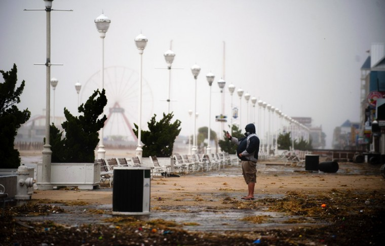 October 29, 2012: A man takes a picture of the storm with his phone from the boardwalk in Ocean City, Maryland as Hurricane Sandy nears landfall in the area. (Jim Watson/AFP/Getty Images)