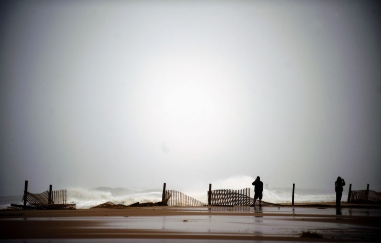 October 29, 2012: Two people stand near the edge of the boardwalk in Ocean City, Maryland as Hurricane Sandy nears landfall in the area. (Jim Watson/AFP/Getty Images)
