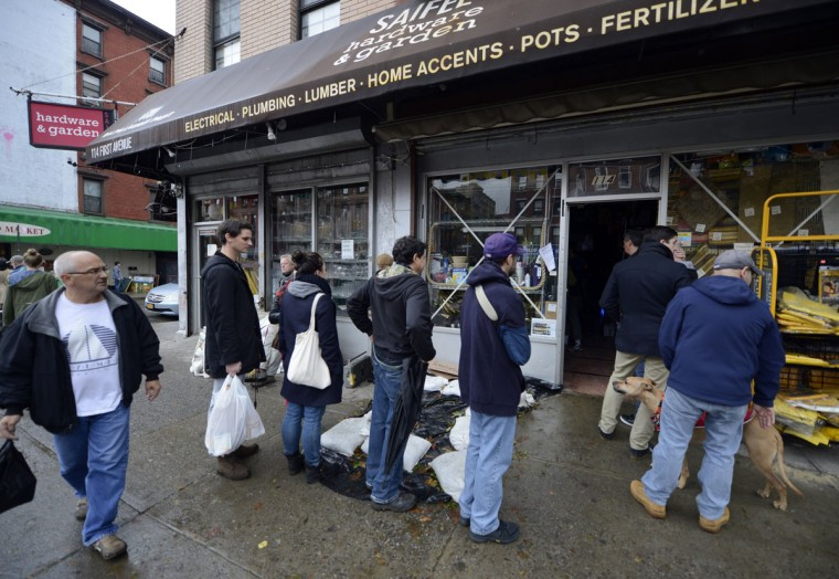 People line up for supplies at a hardware store in the East Village in New York. New Yorkers are coping with the aftermath of Hurricane Sandy, which left large parts of the city without power and transportation. (Timothy A. Clary/AFP/Getty Images)