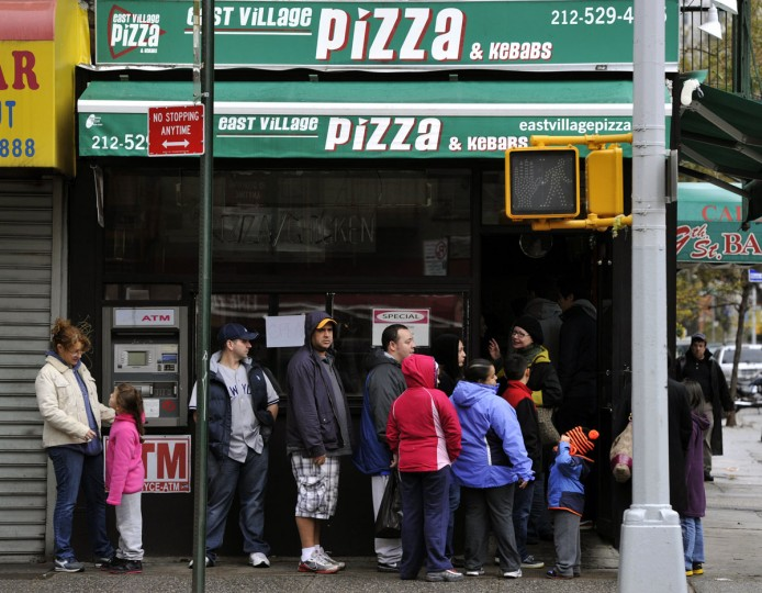 People line up for pizza in the East Village in New York in the aftermath of Hurricane Sandy. New Yorkers are still coping with the effects of the storm, which left large parts of the city without power and transportation. (Timothy A. Clary/AFP/Getty Images)