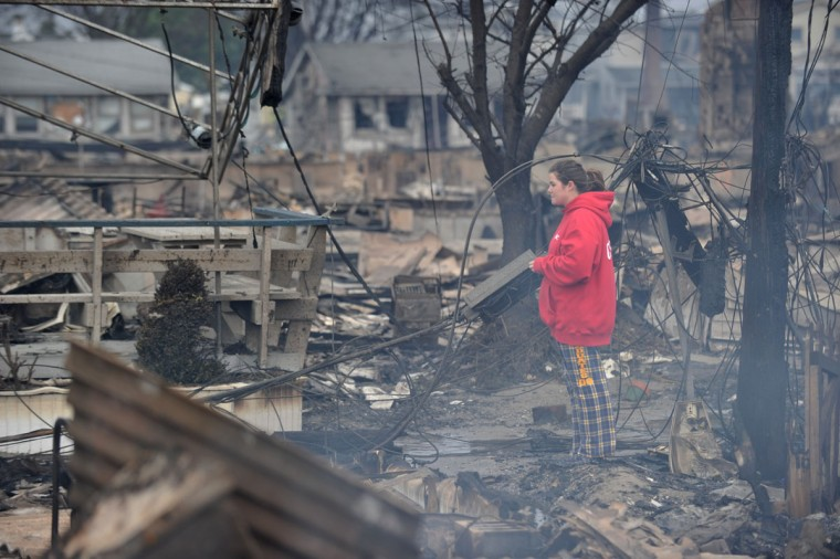 A woman observes still-smoldering rubble in a neighborhood in the Breezy Point area of Queens in New York City. Fire destroyed about 80 homes as a result of Hurricane Sandy, which hit the area on October 29. (Stan Honda/AFP/Getty Images)