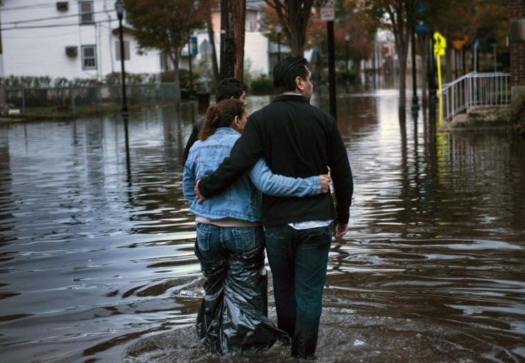 A family navigates their way home after flood waters receded to walkable levels in Little Ferry, New Jersey. Hurricane Sandy, which hit New York and New Jersey particularly hard, left much of the area flooded and without power. (Brendan Smialowski/AFP/Getty Images)