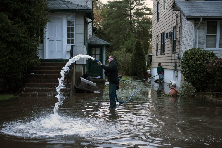 Rocky Minotti uses a pump to remove ten feet of flood water from his family's home in Little Ferry, New Jersey. Hurricane Sandy, which hit New York and New Jersey particularly hard, left much of the area flooded and without power. (Brendan Smialowski/AFP/Getty Images)