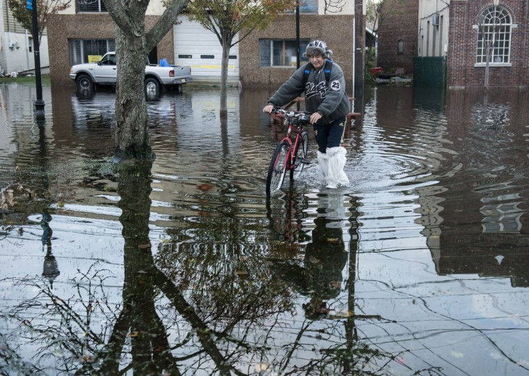 Marco Celdo walks a bike through flood waters in Little Ferry, N.J., while traveling to another town in order to charge his cell phone. Hurricane Sandy, which hit New York and New Jersey particularly hard, left much of northern New Jersey flooded and without power. (Brendan Smialowski/AFP/Getty Images)
