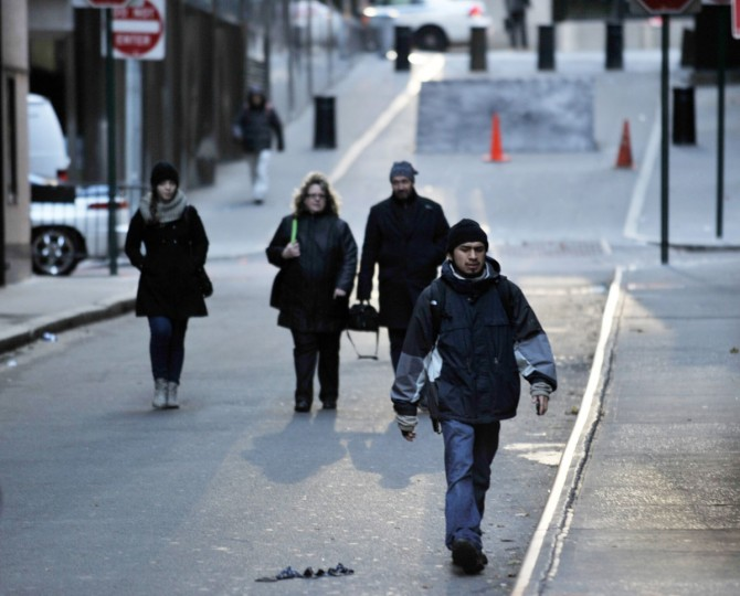 People walk to work on a normally busy street near the New York Stock Exchange. The NYSE opened for training after being closed for two days due to the arrival and aftermath of mega-storm Sandy. (Stan Honda/AFP/Getty Images)