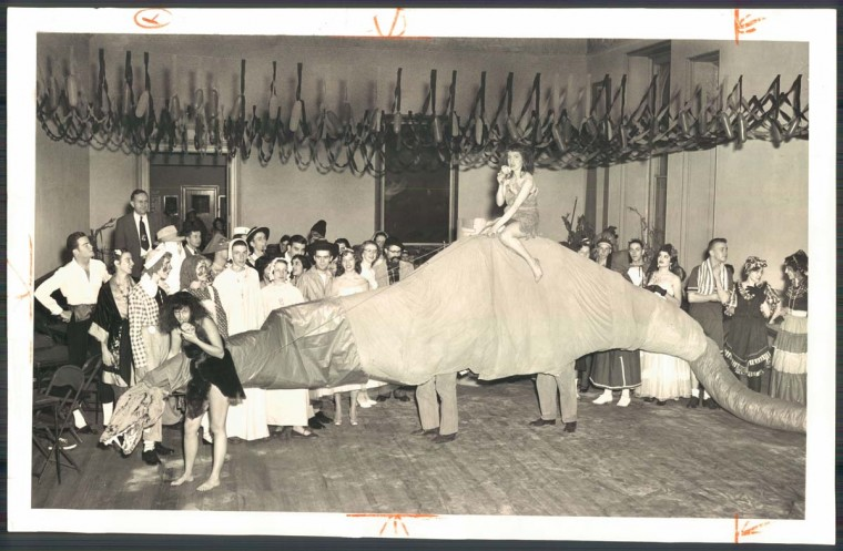 A 36 ft. dinosaur with blinking eyes led by two girls at a Halloween dance.1953. (Dick Stacks/Baltimore Sun)