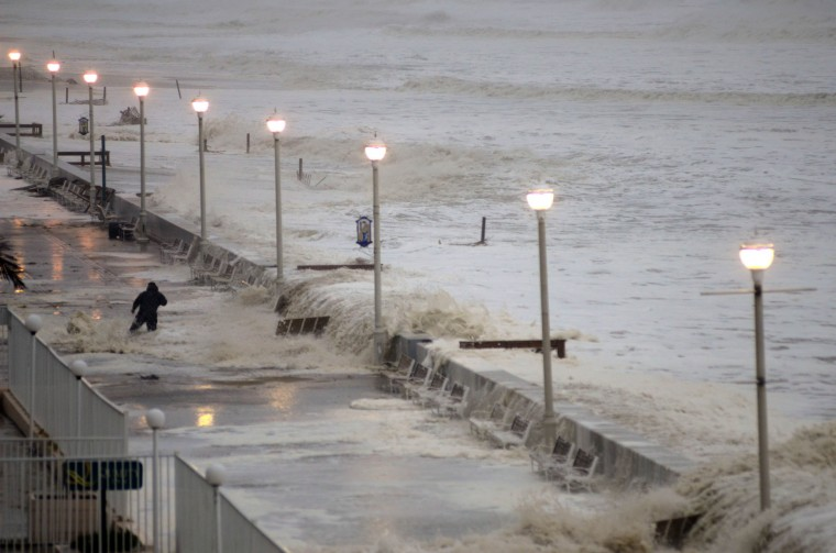 Waiting for landfall: A wave overtakes the seawall, knocking into an observer who is thrown off balance on the boardwalk near 16th Street. (Karl Merton Ferron / Baltimore Sun)