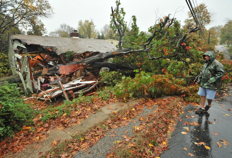 Neighbor Paul Ragan examines the damage to a home at 420 W. Maple Avenue that was crushed by a tree during Hurricane Sandy. (Amy Davis/Baltimore Sun)