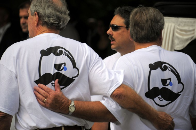 "Aug. 30: 'Scunny' McCusker funeral. Wearing shirts that express a mourning Natty Boh character, pallbearers stand together at the conclusion of the funeral for Patrick ""Scunny"" McCusker, at the Cathedral of Mary Our Queen. (Karl Merton Ferron/Baltimore Sun)"