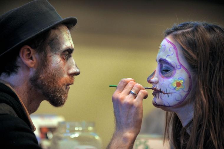 Artist Matt Miurhead of Hampden paints the face of Kori Rabida during the second annual Zombie Gras on Feb. 11, 2012. (Karl Merton Ferron / Baltimore Sun Photo)