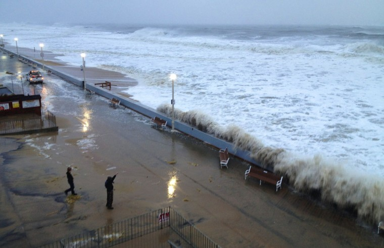 October 29, 2012: Two tourists watch as a wave breaches the seawall while a city truck in background drives along the Ocean City boardwalk as hurricane Sandy begins her track inland. (Karl Mertron Ferron/Baltimore Sun)