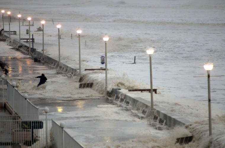 October 29, 2012: A wave overtakes the seawall, knocking into an observer who is thrown off balance on the boardwalk near 16th Street as Hurricane Sandy, now a Category One system, turns towards the eastern seaboard Monday. (Karl Mertron Ferron/Baltimore Sun)