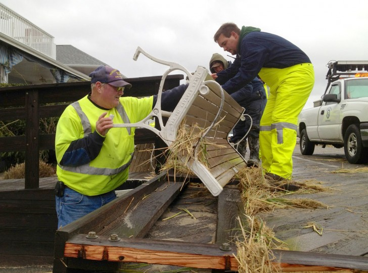 October 30, 2012: Public works crews from Ocean City move one of a number of 300 lb benches on the boardwalk at 10th St. after they were tossed about from ocean waves that breached the seawall from Superstorm Sandy. (Karl Merton Ferron/Baltimore Sun)