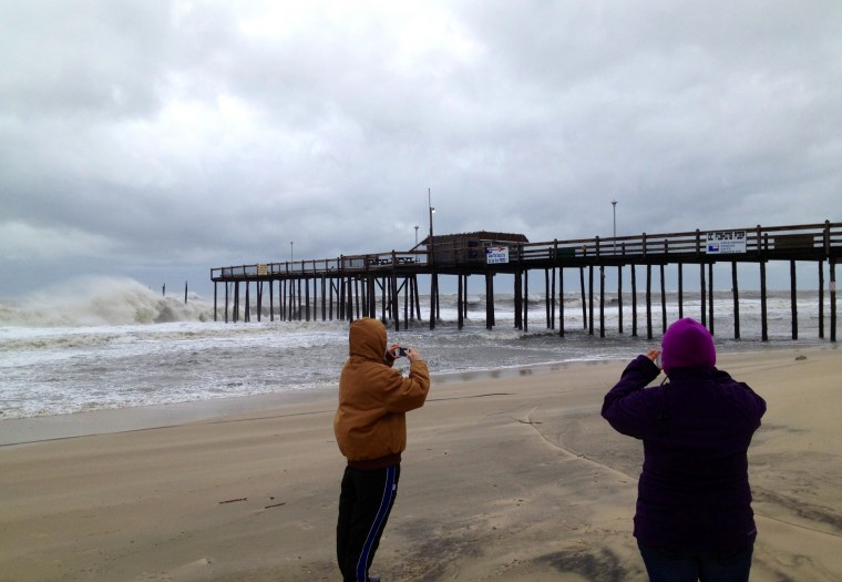 Molly Baysinger, left, and cousin Stacy Jarman take pictures of the damaged Ocean City Fishing Pier that lost up to 100 feet of its structure. (Karl Merton Ferron / Baltimore Sun)