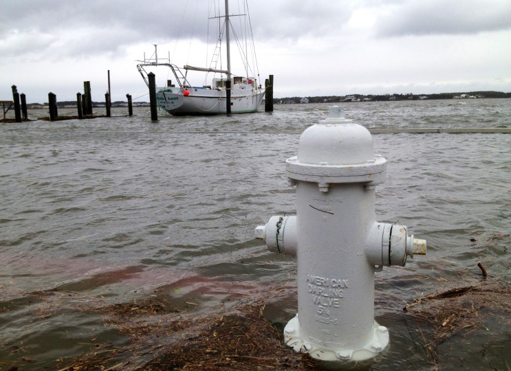 A fire hydrant at Edgewater Ave. and 9th Street is surrounded by water with a sailboat docked in the bay in the background after bay waters breached the seawall in Ocean City. (Karl Merton Ferron / Baltimore Sun)