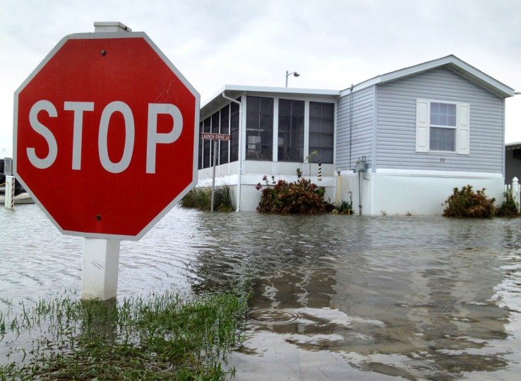 A street sign at a mobile home park stands among trailers surrounded by water. (Karl Merton Ferron / Baltimore Sun)