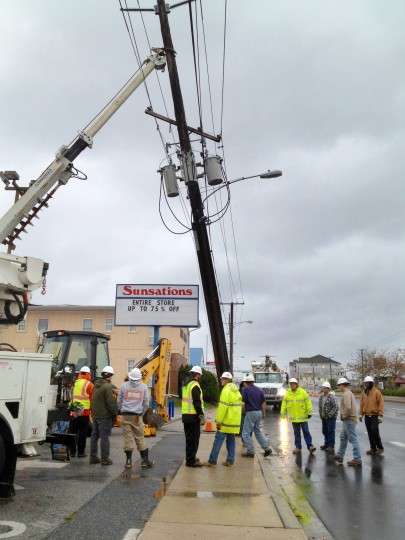 Utility crews standby with a digger truck used to prop up a utility pole at Coastal Highway near 25th St. after winds from Superstorm Sandy cracked the base. (Karl Merton Ferron / Baltimore Sun)