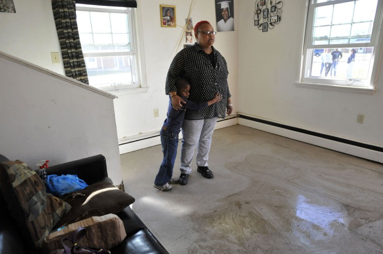 Jerrod Brown, 5, clings to his mother, Kisha Jones, in their Somers Cove Apartments home. They were home when Superstorm Sandy struck, flooding the apartment with several inches of water. (Kim Hairston/Baltimore Sun)
