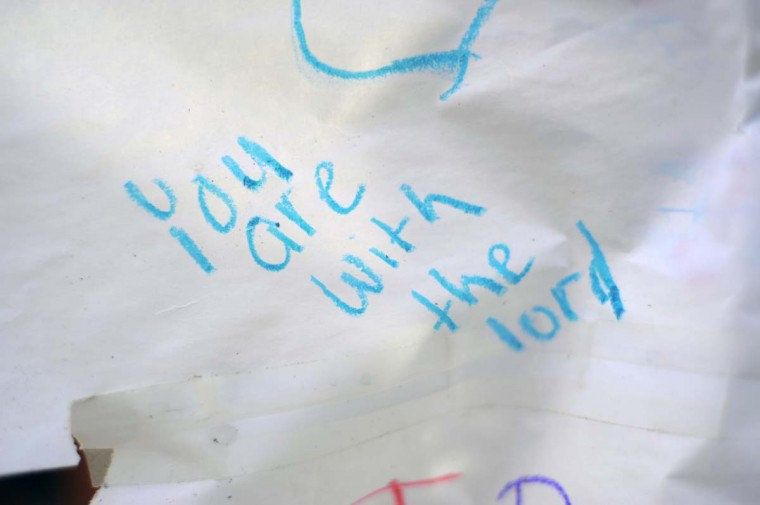 Thoughts of hope and prayer, apparently written by children, rest on display with mylar balloons, stuffed animals and family photos on the front porch at the site of a fatal fire at a townhome on Denwood Avenue. (Karl Merton Ferron/Baltimore Sun)