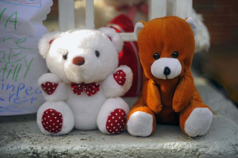 Stuffed animals stand guard on the front porch at the site of a fatal fire at a townhome on Denwood Avenue. (Karl Merton Ferron/Baltimore Sun)
