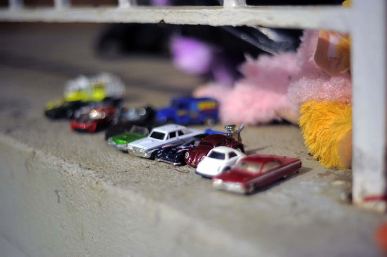 Toy cars are parked together at the site of a fatal fire at a townhome on Denwood Avenue. The blaze killed a grandmother and four children. (Karl Merton Ferron/Baltimore Sun)