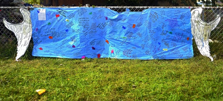 A banner, adorned with paper angel's wings and written with thoughts of children, rests on the chain link fence at the site of a fatal fire at a townhome on Denwood Avenue. Family members apparently were spread among the three bedrooms on the second floor, with many of the children in a rear room. The fire started in the rowhouse's basement, and spread upward, fire officials said. City Fire Chief James S. Clack said interviews with family members who escaped the fire and an initial investigation indicated the home had no working smoke detectors.(Karl Merton Ferron/Baltimore Sun)