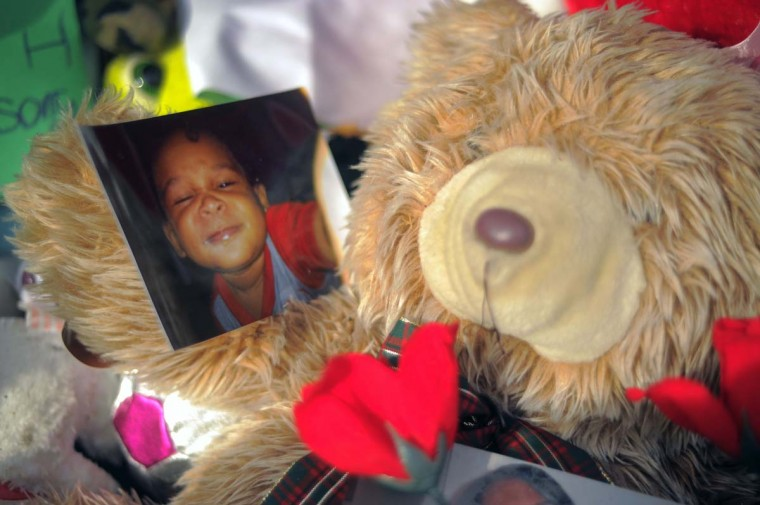 Family photos are part of the display of affection along with toys and thoughts on the front porch at the site of a fatal fire at a townhome on Denwood Avenue. The blaze killed a grandmother and four children. (Karl Merton Ferron/Baltimore Sun)