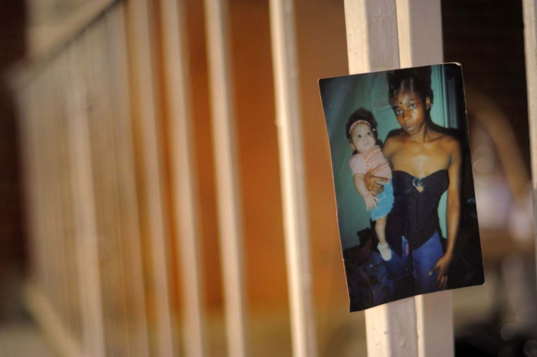 Family photos are part of the display of affection along with toys and thoughts on the front porch at the site of a fatal fire at a townhome on Denwood Avenue. (Karl Merton Ferron/Baltimore Sun)