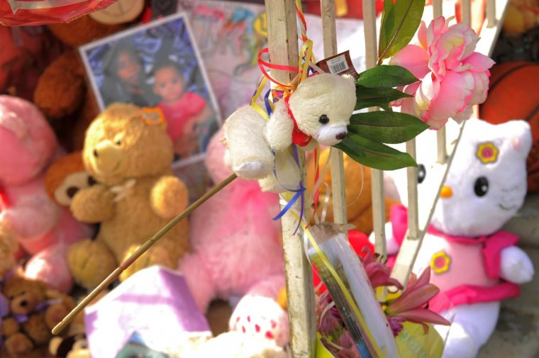 Family photos are part of the display of affection along with toys and thoughts on the front porch at the site of a fatal fire at a townhome on Denwood Avenue. (Karl Merton Ferron/Baltimore Sun) [
