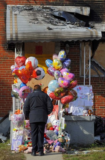 Cinder Littlejohn stands among the stuffed animals, mylar balloons and family photos that decorate the charred shell of a townhouse, the scene of what remains of a fatal fire on Denwood Avenue. (Karl Merton Ferron/Baltimore Sun)