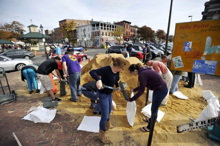 Katie Keane, Fells Point, and Alaina Graves, Canton, fill bags with sand to protect their homes from Hurricane Sandy. Keane lives a block and a half from the water. (Kim Hairston/Baltimore Sun Photo)