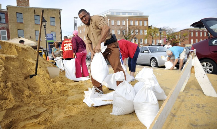 Carl Bugess, Pikesville, lifts sand bags into a pile at the foot of Broadway on Thames Street. He is filling 18 sand bags to protect the dance studio his daughter attends and provide a barrier from the waters of the Jones Falls. (Kim Hairston/Baltimore Sun Photo)