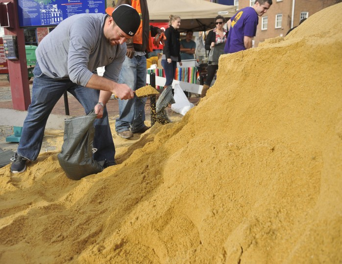 Marcus Lages, Fells Point, prefers a trowel to a shovel to fill sand bags at the foot of Broadway at Thames. He is creating the barriers to protect his Fleet Street home from Hurricane Sandy. (Kim Hairston/Baltimore Sun Photo)
