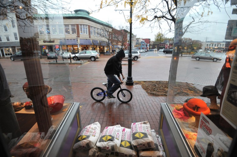 A bicyclist rides by Hats in the Belfry on Main St. The store has already stacked sandbags outside one of their doors. Annapolis merchants get ready for Hurricane Sandy. (Algerina Perna/Baltimore Sun)