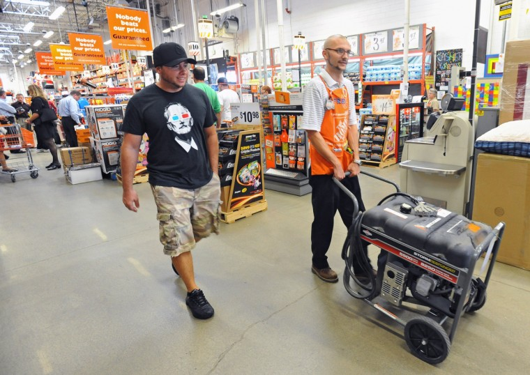 James Boyd, of Essex, left, bought the last gas generator at the Eastern Avenue Home Depot as Paint Department Supervisor Fred Jogerit, right, help roll the generator to the check out line. The store sold out of the over 50 generators it had in stock as Baltimore City and County residents pick up emergency supplies such as flash lights, batteries and gas generators to prepare for the weekend arrival of Hurricane Sandy. (Kenneth K. Lam/The Baltimore Sun)