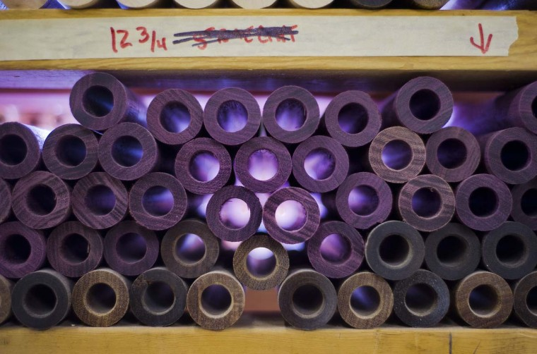 Purple heart and cumaru rest beneath curly maple wood for handles at Joss Cues. (Karl Merton Ferron/Baltimore Sun)