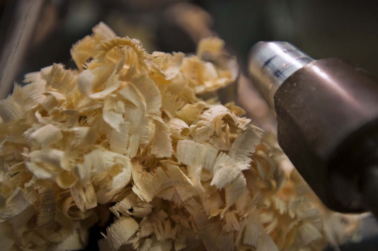 Curly maple shavings rest from the turning of cue handles at Joss Cues. When Joss Cues was founded Dan and his partner worked with one ancient manual lathe, a butcher-shop band saw, one drill press, and a single work bench, the two former road pool players took some of contemporary cue making's first steps away from the traditional four-prong design to many innovative concepts.